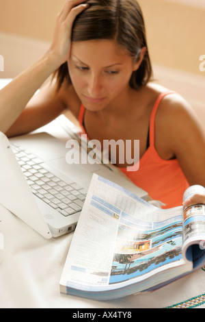woman looking for holiday via the internet - Stock Photo