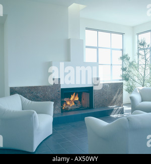 Lighted fire in granite fireplace in modern white living room with white armchairs and grey tiled floor - Stock Photo