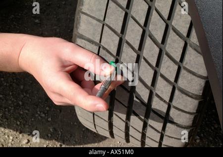 Checking tyre tread depth on a car. - Stock Photo
