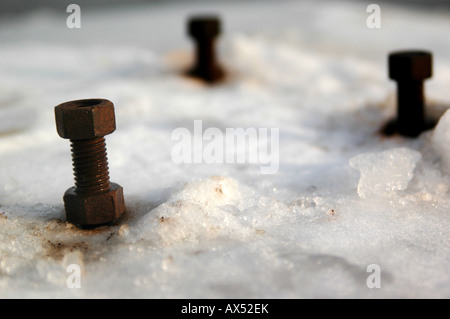 Three rusted bolts frozen in snow - Stock Photo