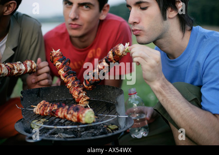 Three young men grilling close to a tent - Stock Photo