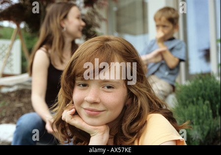 Little girl, portrait, brother and sister in background - Stock Photo