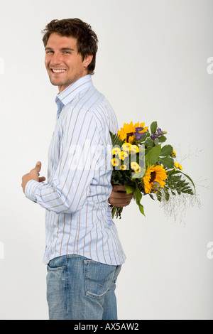 Young man holding bouquet of flowers behind back, smiling, close-up, portrait - Stock Photo