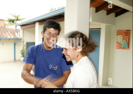 Young woman and man dancing boisterously in front of a house, Asuncion, Paraguay, South America - Stock Photo