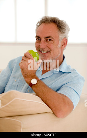 Mature man sitting on sofa holding apple, smiling, portrait - Stock Photo