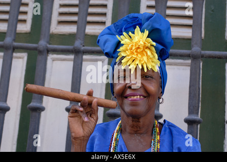 Woman wearing traditional clothes holding a cigar, Havana, Cuba - Stock Photo
