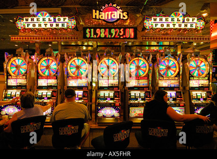 Gamblers sitting in front of slot machines in Harrah's Casino on the Strip, Las Vegas Boulevard, Las Vegas, Nevada, - Stock Photo