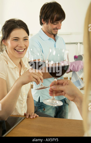 Woman toasting, man working in background, smiling - Stock Photo