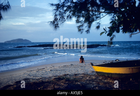 Buzios, Rio de Janeiro State, Brazil. Girl sitting on a beach looking out to sea with a small boat in the foreground. - Stock Photo