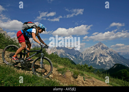 Female mountain biker, Mt. Antelao in the background, Dolomites, Northern Italy, Europe - Stock Photo