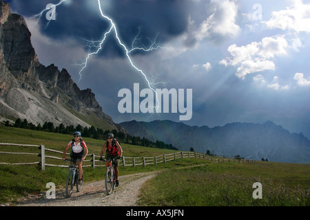 Female mountain bikers during a thunderstorm, lightning in the background, Dolomites, Northern Italy, Europe - Stock Photo