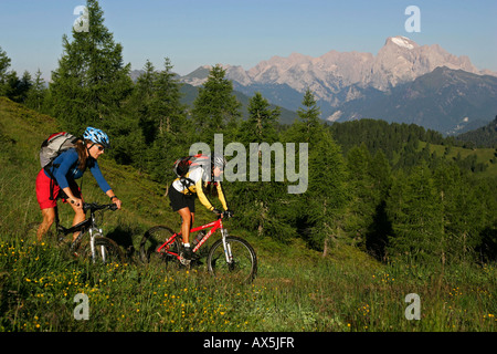 Female mountain bikers, Mt. Marmolada in the background, Dolomites, Northern Italy, Europe - Stock Photo