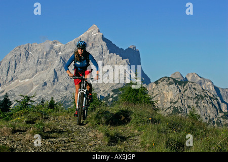 Female mountain biker, Mt. Civetta in the background, Dolomites, Northern Italy, Europe - Stock Photo