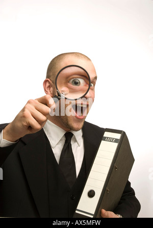 Young man carrying binder holding magnifying glass in front of his face - Stock Photo
