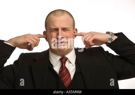 Young man plugging his ears - Stock Photo