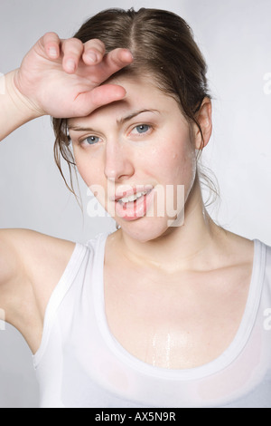 Exhausted young woman after a workout, wiping the sweat from her forehead with her hand - Stock Photo