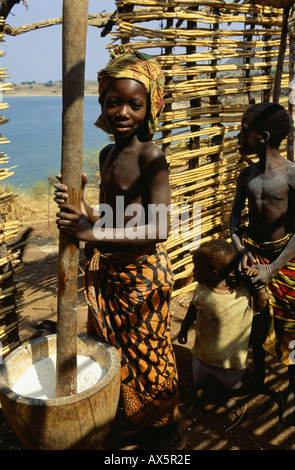 Yumba, Tanzania. Girl pounding cassava in a wooden bowl in a part finished house with her brother and sister. - Stock Photo