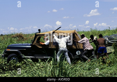 Chipundu, Zambia. Four wheel drive Jeep and trailer needing a push to escape from the mud 'cross country' in a swamp. - Stock Photo