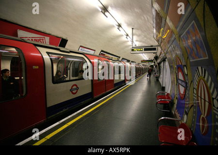Tube logo, colorful tiles and train arriving at London Arch underground station, London, England, UK, Europe - Stock Photo