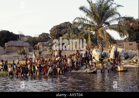 Kalepo, Tanzania. Village children knee-deep at the water's edge waving; Lake Tanganyika. - Stock Photo