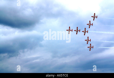 Nine of the red and white Canadian Snowbirds fly in formation leaving trails of white smoke - Stock Photo