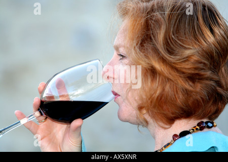 Young lady drinking a glass of red wine - Stock Photo