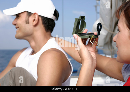 Woman putting her hand on man's shoulder, using a compass - Stock Photo
