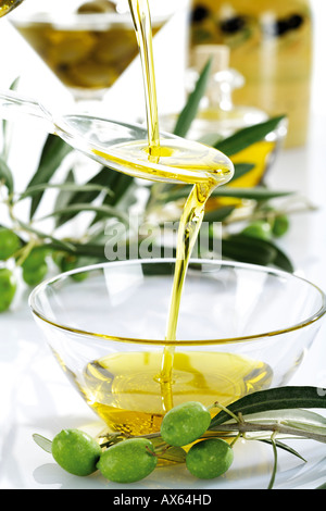 Fresh green olives and olive oil in glass bowl - Stock Photo