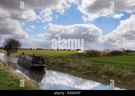 Narrow boat navigating the Wendover Cut of the Grand Union Canal on a bright early spring day - Stock Photo