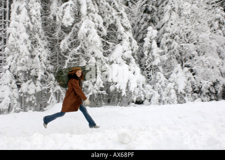 Young woman carrying Christmas tree on shoulders in snow, smiling - Stock Photo