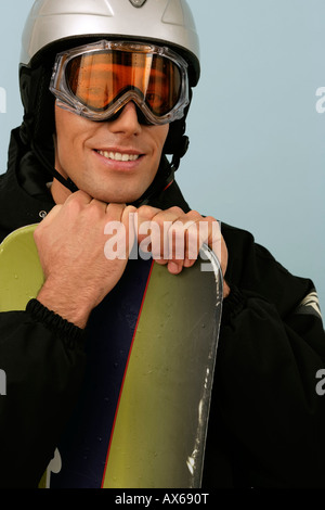 A man wearing ski goggles and a safety helmet  leaning on a snowboard - Stock Photo