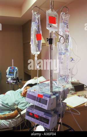 Woman connected to IV tubes in hospital recovery room - Stock Photo