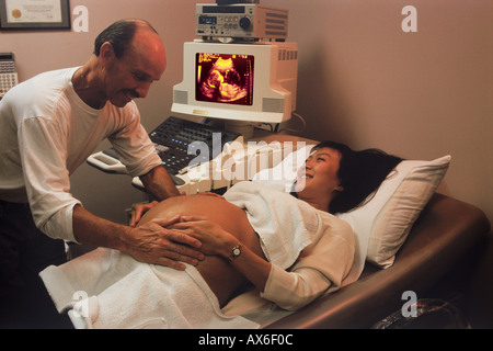 Husband and pregnant wife during ultrasound test with fetus on screen - Stock Photo