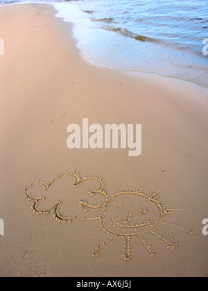 Smiling sun face and could drawn on sand - Stock Photo