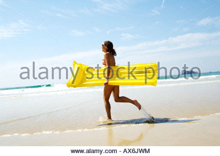 Side profile of girl running with air bed on beach - Stock Photo
