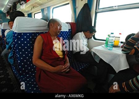 A monk sleeps on the Tibet train Tibet railway - Stock Photo