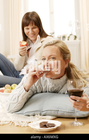 Woman looking at her mother eating chocolate - Stock Photo