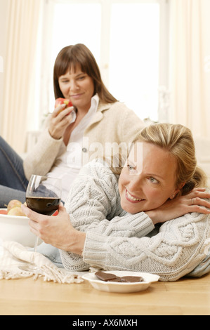 Woman looking at her mother holding glass of wine - Stock Photo