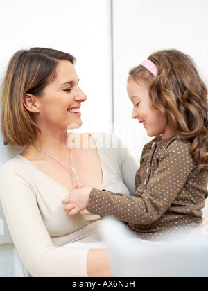 Close-up of woman looking at her daughter and smiling - Stock Photo