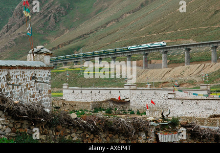 A train passes over a bridge next to a Tibetan village on the Tibet railway, which opened in July 2006. Tibet train - Stock Photo