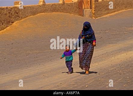 Moroccans, Moroccan, Moroccan woman, Berbers, Berber, Berber woman, mother and son, walking, town of Merzouga, Merzouga, - Stock Photo