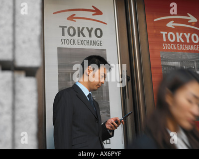 A Japanese businessman with mobile phone outside the Tokyo stock exchange dials a number while other business people - Stock Photo