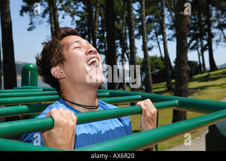 Young man on monkey bars - Stock Photo