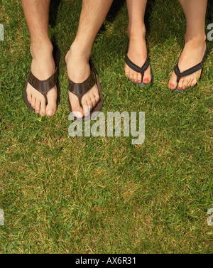 Male and female feet in sandals - Stock Photo