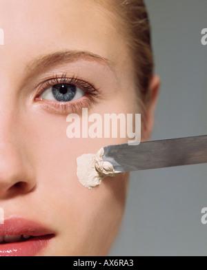 Woman applying facial mask - Stock Photo
