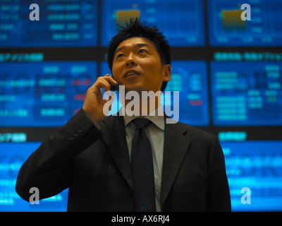 A Businessman talks on his mobile phone inside the electronic Tokyo Stock Exchange Tokyo Japan Released - Stock Photo