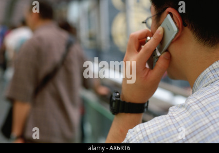 A man talks on a mobile cell phone while walking to work on the Hong Kong Central escalator the longest in the world - Stock Photo