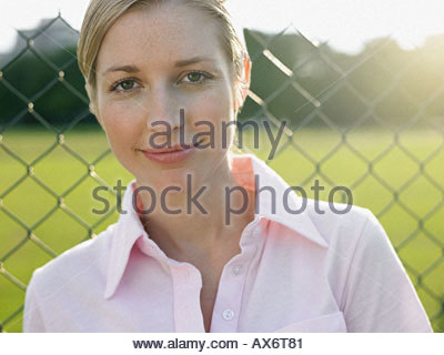 Woman standing by wire fence - Stock Photo