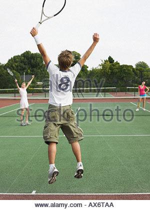 People celebrating on tennis court - Stock Photo