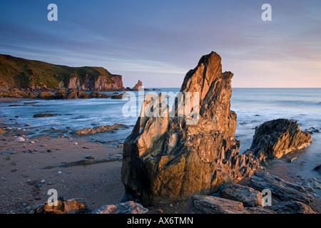 Jagged rocks on the South Devon coast at Bantham - Stock Photo